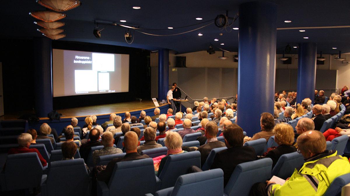 Foto på föreläsningssal med många åhörare. Stolar, tak och pelare är i djup blå färg.
