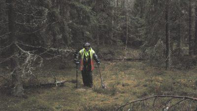 En arkeolog står med utrustning i regnet mitt i skogen.