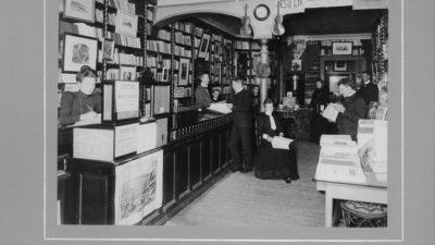 Svartvit foto med interiör från Jönköpings bokhandel. Flera personer figurerar på bilden