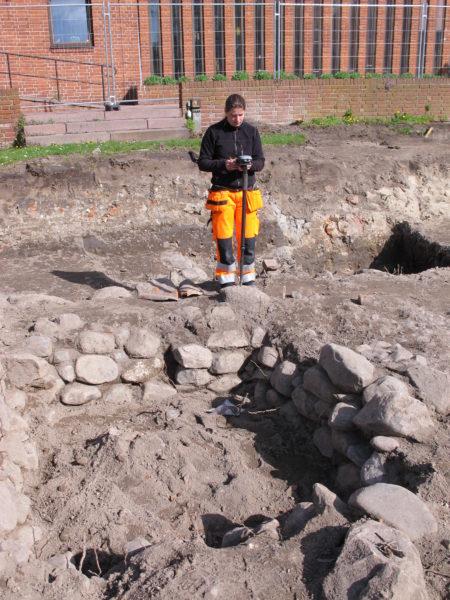 Therese mäter in den stenskodda brunn som Svend och Niels byggde för fyrahundra årsedan