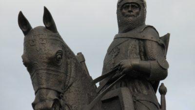 En staty med en person i rustning, hjälm och svärd sitter på en häst som även den är utrustad.