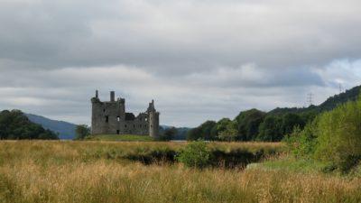 Gråa moln. Lusa höga grässtrån över en äng. Fluffigt gröna träd på höger och vänster sida. I mitten finner vi en ruin från ett slott och bakom ligger en sjö.