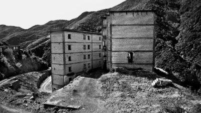 Svartvitt foto på två höga byggnader omvälvt av berg.