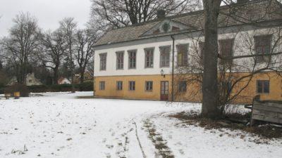 Bild över Rosenlunds herrgård. Snö på marken och stora gamla träd här och där omkring herrgården.