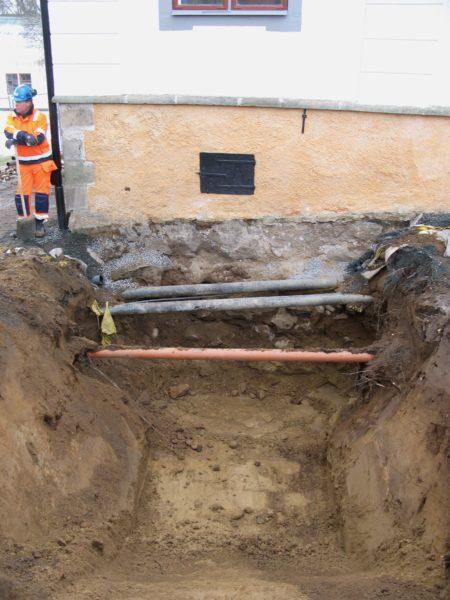 En grop har grävts fram vid sidan av herrgården. Tre rör syns gå över gropen. En arbetare står vid vänster kant.