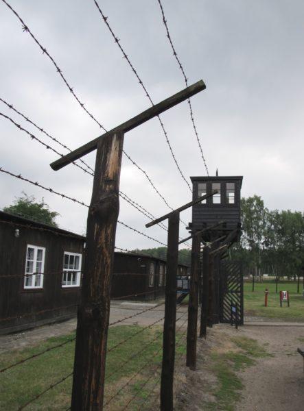 Bild på en grind med ett vakttorn samt taggtrådsstängsel.