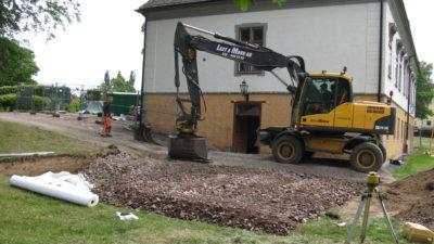 Bild på herrgård med en grävskopa framför.