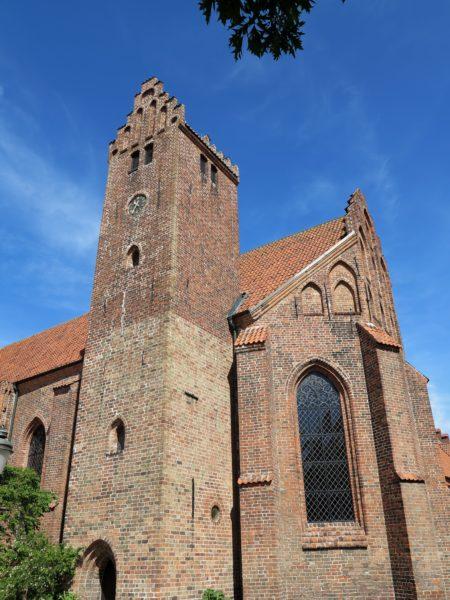 Bild på ett kloster gjort a tegel. Ett torn syns mot blå bakgrund.