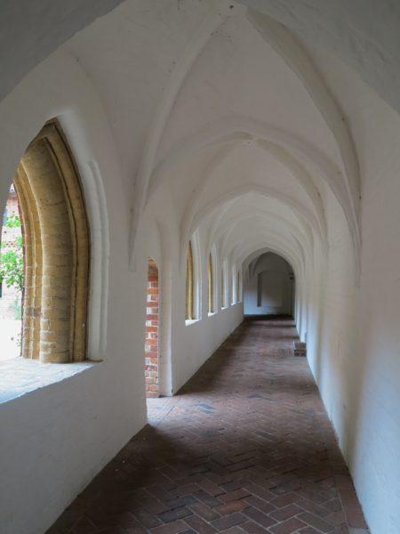 Bild över en korsgång, korridor med valv i mot taket. Väggar och tak är vita medans golvet är lagt i tegel enligt ett mönster.