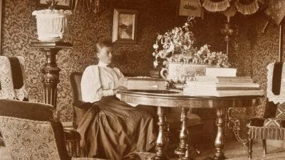 Hanna Friberg i sitt hem vid ett bord fullt av album och bokverk