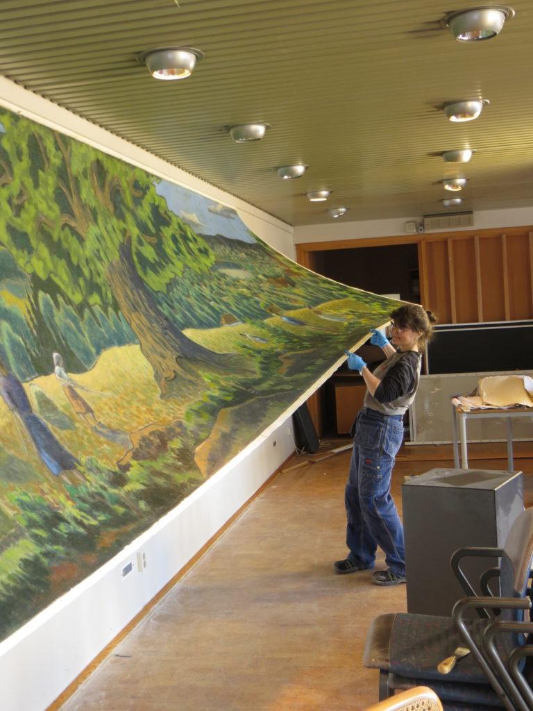 Målningen har lossats från väggen, utom i övre kanten.