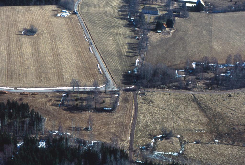 Flygfoto från Edshult med säteribyggnaden i bakgrunden, kyrkoplatsen till vänster och borgruinen i förgrunden.