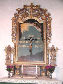 En altaruppsats. Ramen är i guld och har många olika detaljer. I ramen är en person korsfäst.