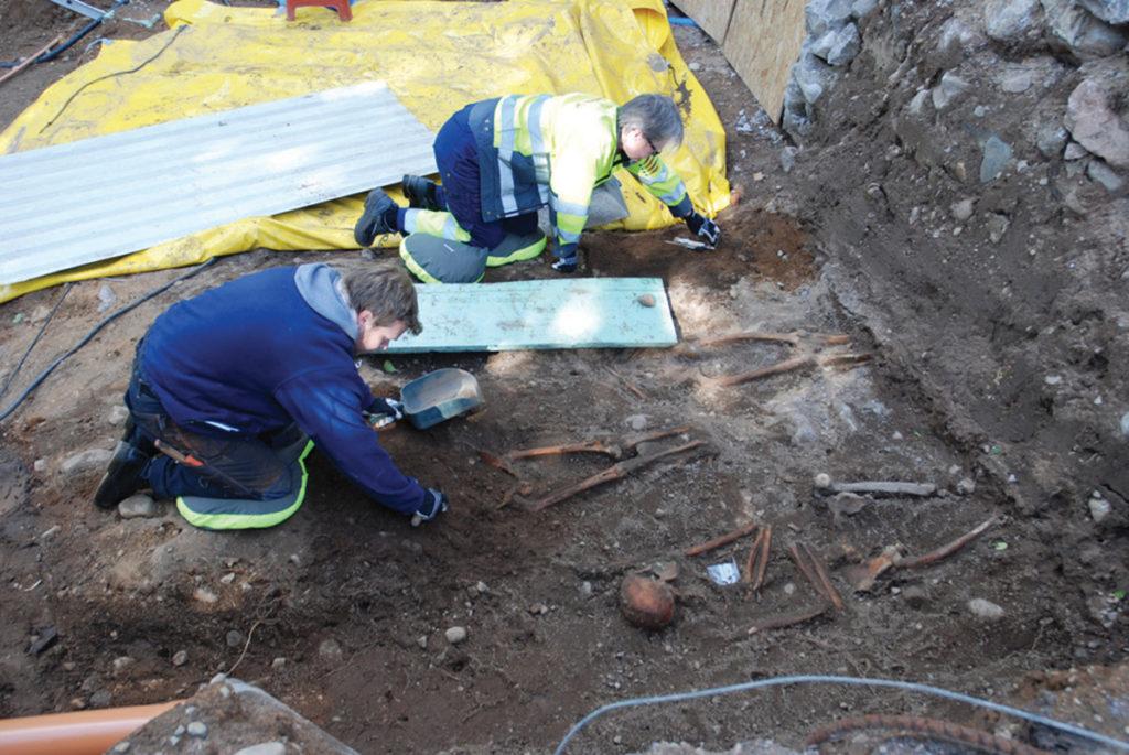 Arkeologer undersöker gravar vid kyrkan.