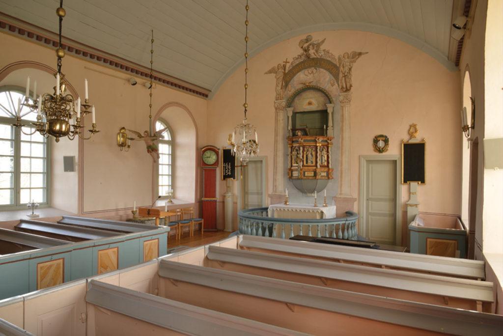 Interiören från Utvängstorps kyrka med predikstolen över altaret och dopängeln hängande över dopfunten.