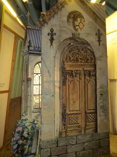 Målad kuliss med kyrk-gavel. Den målade fasaden är grå med detaljer.