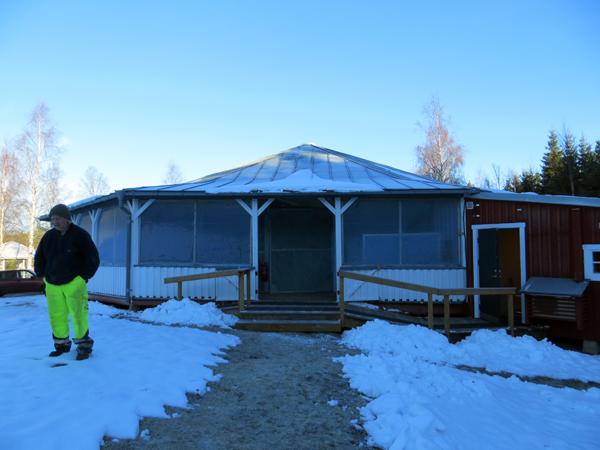Ett runt hus utomhur. Framför står en person och på marken ligger det snö.