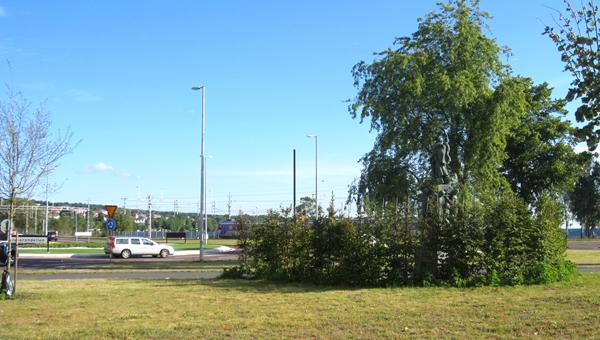 En gräsplätt med gröna träd. En väg syns i bakgrunden.