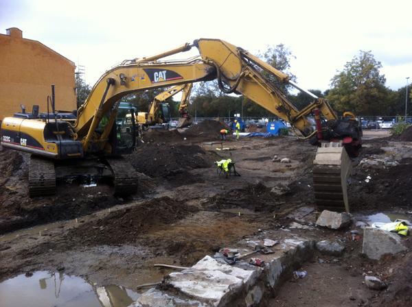 En gul grävmaskin gräver i jorden.