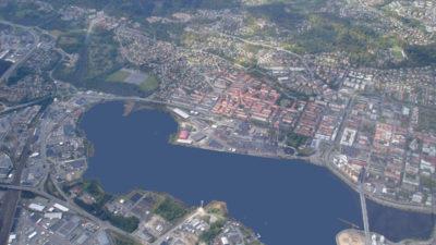Flygbild över en stad. På bildens syns en stor sjö, hus och vägar.