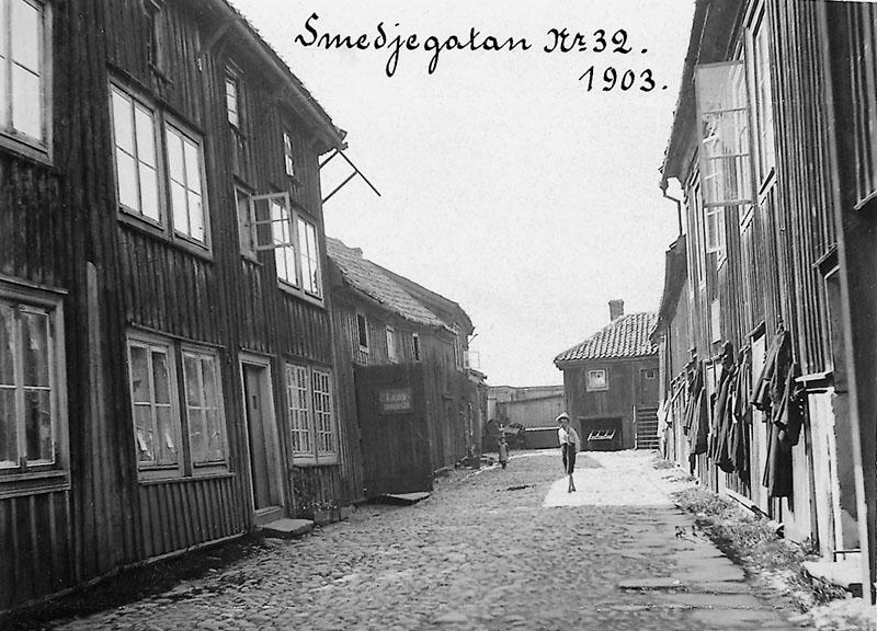 Svartvit bild på gamla trähus. Mellan trähusen går en liten gata med kullersten.
