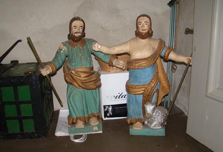 Två träskulpturer med målade gröna och blå dräkter.