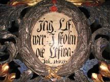 Detaljer från gravskriftet. En rund ring med text i.