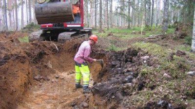 Arkeolog gräver ut ett röjningsröse i skogsmark. Grävmaskin i bakgrunden.