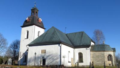 Vitkalkad kyrka med blå himmel bakom.