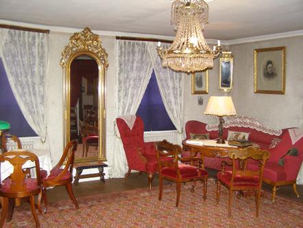 Rum med röda möbler, kristallkrona som taklampa och spegel med guldram.