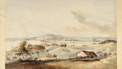 Landskap med massor av kullar och ett hus.