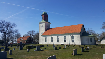 En ljus kyrka med tegelrött tak, gravstenar på kyrkogårdens gräsmatta framför.