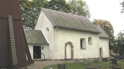 Liten vit kyrka med olika stora fönster. Träd bakom kyrkan och gravstenar på gräsmatta framför.