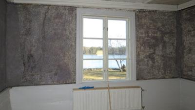 Grå vägg inomhus med fönster och utsikt mot en sjö.