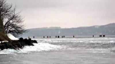En sjö som är frusen till is. Till vänster på land finns ett träd.