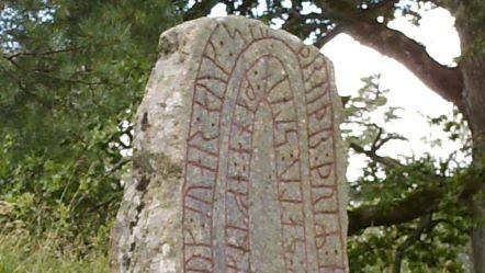 En stor sten med röd inristad skrift i sig. Stenen står i skogen bland gräs och träd.