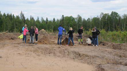 Nio personer står på en jordig mark i skogen.