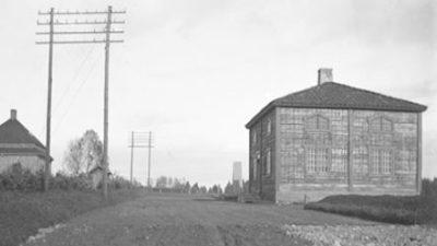 En grusad väg. Till vänster står det två el-ledare. Till höger står ett fyrkantigt hus.