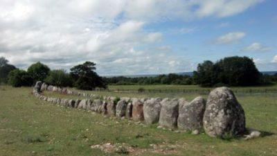 Stenar står uppradat på en platt grön mark. Bortom stenarna finns det gröna träd.