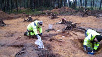 Två personer sitter ner och gräver i marken. Personerna har på sig gula jackor.
