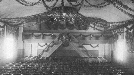 En sal och i taket hänger det en stor takkrona och annat pynt. På golvet står stolar i rad.