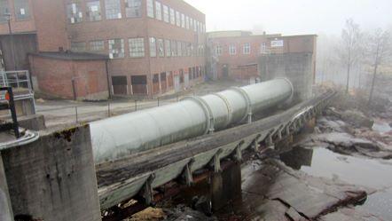 En fabrik med trasiga fönster. Bredvid fabriken ligger en flottningsränna och en stor tub av stål.