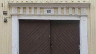 Bild på en träport. Porten är brun med vit ram. Huset är ljusgult.