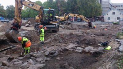 Två grävskopor gräver i marken. Två personer står framför grävskoporna och gräver med spade.