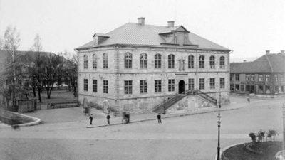 Gammal bild av en tegel byggnad. Bilden är svartvit personer går utanför byggnaden.