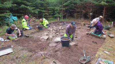 Personer sitter i skogen gräver i marken. På marken ligger det redskap.