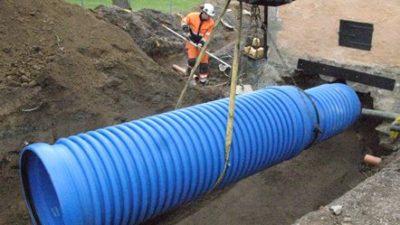 Ett stort blått rör som håller på att sänkas ner i marken.
