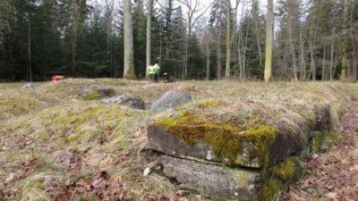 En stengrund med mossa på. Längre bort från stengrunden står två människor i gula jackor.
