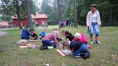 Nio barn sitter på huk eller står på knä på en gräsyta och ristar runor. En vuxen står bredvid. I bakgrunden syns en hembygdsgård samt ytterligare en grupp med barn i aktivitet.