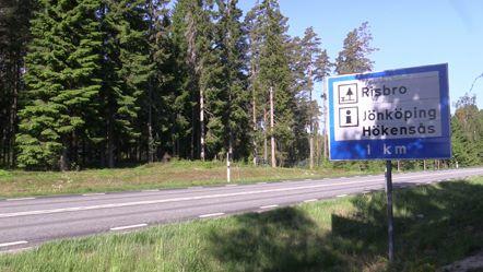 På andra sidan en bilväg syns en liten kulle och bakom den skog. I förgrunden syns en blåvit vägskylt med innehållet Rastplats Risbro, Informationsplats Hökensås 1 km.